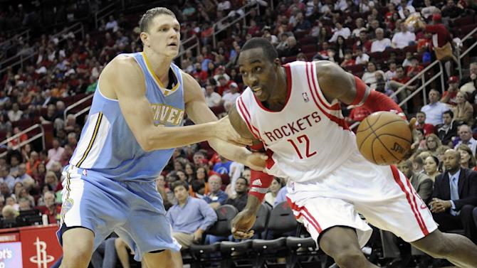 Houston Rockets' Dwight Howard (12) is grabbed by Denver Nuggets' Timofey Mozgov in the second half of an NBA basketball game Saturday, Nov. 16, 2013, in Houston. The Rockets won 122-111