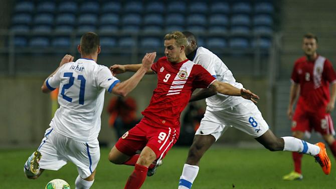 Gibraltar's Adam Priestley, centre, vies for the ball with Slovakia's Martin Juhar, left, and Karim Guede during a friendly soccer match between Gibraltar and Slovakia at the Algarve stadium in Faro, southern Portugal, Tuesday, Nov. 19, 2013. Gibraltar played its first international soccer match as a new full member of the UEFA after they were accepted in May. The match ended in a 0-0 draw