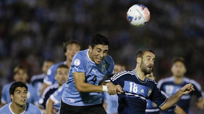 Argentina's Rodrigo Palacio, right, fight for the ball with Uruguay's Jorge Fucile during a 2014 World Cup qualifying soccer match  in Montevideo, Uruguay, Tuesday, Oct. 15, 2013