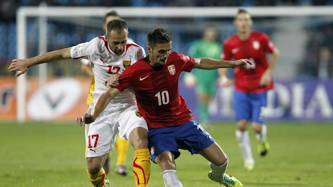 Serbia's Dusan Tadic, right, challenges for the ball with Macedonia's Ostoja Stjepanovic during their World Cup 2014 Group A qualifying soccer match at the City Stadium in Jagodina, Serbia, Tuesday, Oct. 15, 2013