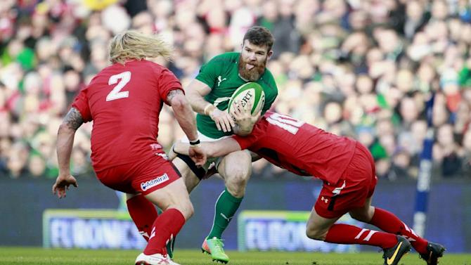 Ireland's Gordon D'Arcy, center, is tackled by Wales' Rhys Priestland, right, and Richard Hibbard, left, during their Six Nations Rugby Union international match at the Aviva Stadium, Dublin, Ireland, Saturday, Feb. 8, 2014