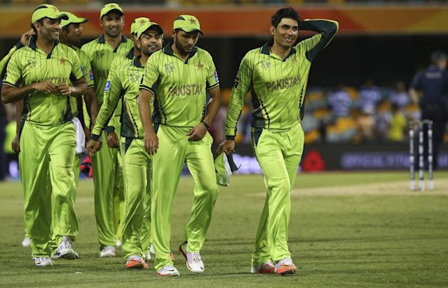 Pakistan's players led by skipper Misbah-ul-Haq, right, walk back after defeating Zimbabwe in the Pool B Cricket World Cup match in Brisbane, Australia, Sunday, March 1, 2015. (AP Photo/Tertius Pi