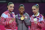 US gymnast Gabrielle Douglas (C) poses on the podium with Russia's gymnast Victoria Komova (R) and Russia's gymnast Aliya Mustafina after winning the artistic gymnastics women's individual all-around final at the 02 North Greenwich Arena in London during the London 2012 Olympic Games. Douglas won ahead of Komova and Mustafina