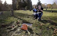 "In this Nov. 17, 2014 photo, Rob Robertson wipes away tears as he sits with his wife Linda while they visit the grave of their son, Ryan, in Issaquah, Wash. The couple, evangelical Christians, brought their son to ""reparative therapy"" when he came out to them as gay. His sexual orientation didn't change, and he became addicted to drugs and eventually died of an overdose. The Robertsons are now dedicated to helping other evangelical parents accept their gay children. (AP Photo/Elaine Thompson)"