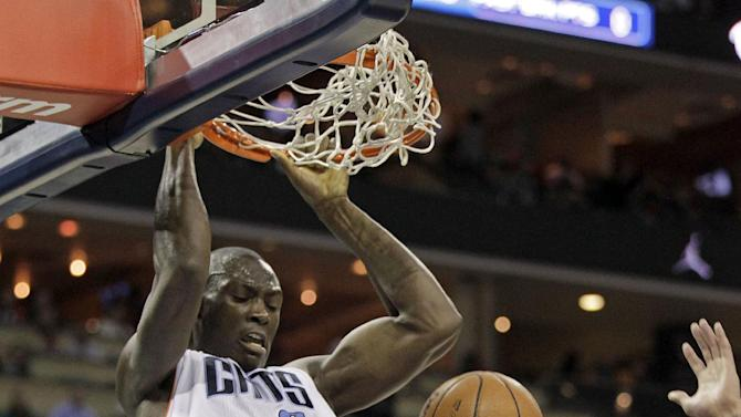 3Charlotte Bobcats' Bismack Biyombo (0) dunks over Los Angeles Lakers' Robert Sacre (50) during the first half of an NBA basketball game in Charlotte, N.C., Saturday, Dec. 14, 2013