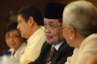 Moro Islamic Liberation Front (MILF) chief negotiator, Mohagher Iqbal (C), attends a meeting of the Transition Commission in Manila, on April 3, 2013. The Philippine government said on Friday it hoped to resume talks with Muslim (MILF) rebels early next month to kickstart negotiations for a peace settlement that looked to have stalled in recent months