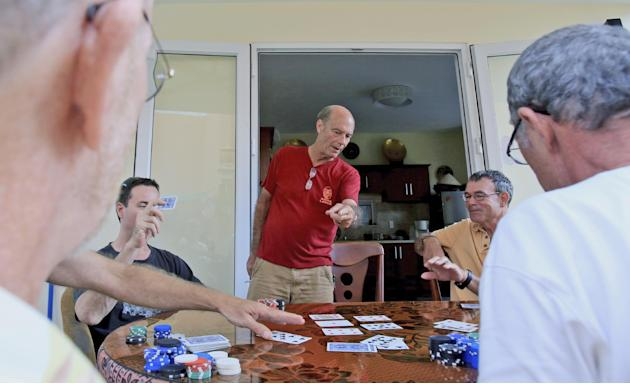 In this April 11, 2015, photo, Bill Ervin, a former U.S. Marine from Colorado who now runs a travel company with his Vietnamese wife, reacts while playing poker with fellow Vietnam war veterans at his