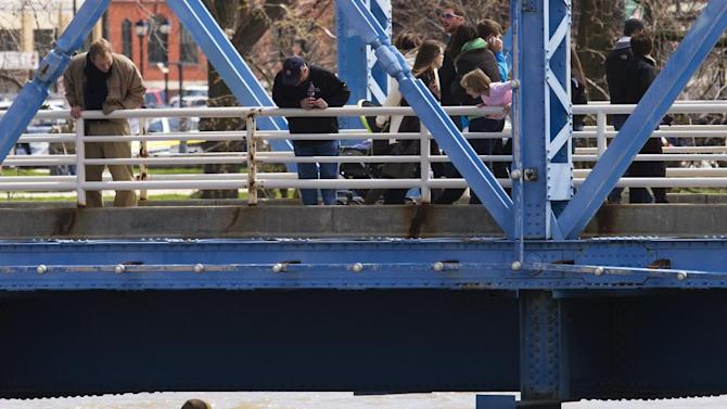 Spectators watch as a kayaker ducks underneath the blue bridge on the Grand River in downtown Grand Rapids, Mich., Sunday, April 21, 2013. The rising Grand River has driven hundreds of people from their homes in several western Michigan communities and was pushing Sunday toward a record high near Grand Rapids. (AP Photo/MLive.com, Sally Finneran)
