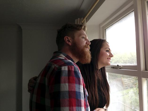 James Renhard and Vicki Clayton look out of a window of their new rented flat in Lewisham, south-east London
