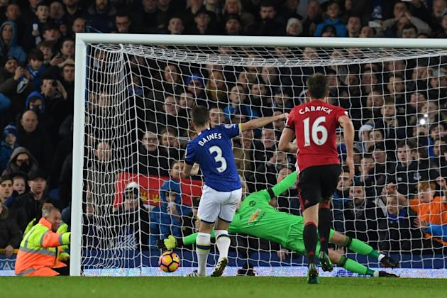 Everton's defender Leighton Baines (L) scores his penalty past the diving Manchester United's goalkeeper David de Gea during the English Premier League football match between Everton and Manch