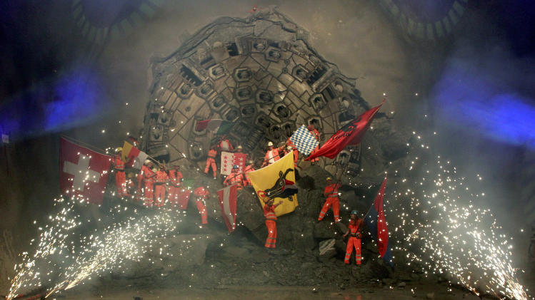 Miners celebrate as fireworks explode after a giant drill machine broke through the rock at the final section Sedrun-Faido, at the construction site of the NEAT Gotthard Base Tunnel