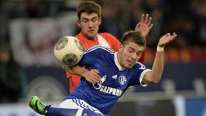 Schalke's Roman Neustaedter, front, and Mainz's Stefan Bell challenge for the ball during the German Bundesliga soccer match between FC Schalke 04 and FSV Mainz 05 in Gelsenkirchen,  Germany, Friday, Feb. 21, 2014