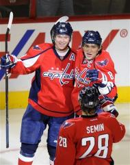 Washington Capitals center Nicklas Backstrom, left, of Sweden, celebrates his goal with teammates Alex Ovechkin (8), of Russia, and Alexander Semin (28), of Russia, during the second period of an NHL hockey game against the Buffalo Sabres, Friday, Dec. 30, 2011, in Washington. (AP Photo/Nick Wass)