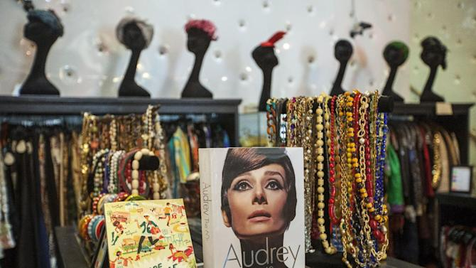 "In this photo taken Thursday, Feb. 21, 2013, a 1960's fashion book of actress Audrey Hepburn is displayed with vintage jewelry at ""The Way We Wore,"" a Hollywood high-end vintage store owned by Doris Raymond in the La Brea District of Los Angeles. Raymond's vintage clothing and accessories store is featured in the reality TV series, ""L.A. Frock Stars,"" which debuts March 7, 2013 on the Smithsonian Channel. (AP Photo/Damian Dovarganes)"