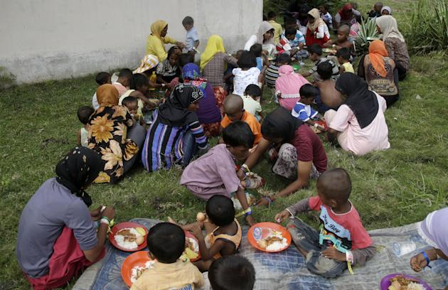 In this Saturday, May 23, 2015, photo, Ethnic Rohingya women and kids gather to eat at a temporary shelter in Bayeun, Aceh province, Indonesia. Thousands of migrants have washed ashore in Indonesia, M