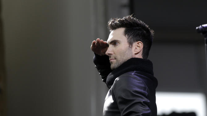 Adam Levine salutes as he performs with Maroon 5 at the New Orleans Jazz and Heritage Festival in New Orleans, Friday, May 3, 2013. (AP Photo/Gerald Herbert)