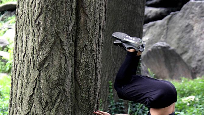 Taylor Lautner flipping around against a tree at