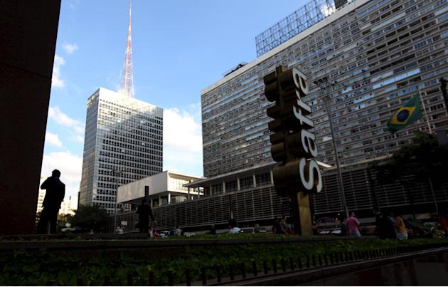 A man talks on his mobile phone next to the  Banco Safra SA headquarter in Sao Paulo