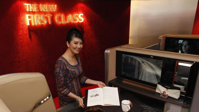 A Singapore Airlines Ltd stewardess poses at a first class cabin seat during the launch of their new generation of cabin products at Changi Airport in Singapore