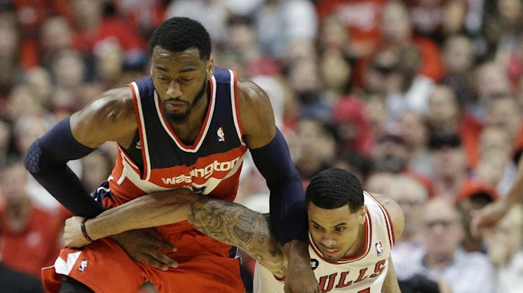 Washington Wizards guard John Wall, left, steals the ball from Chicago Bulls guard D.J. Augustin during the first half in Game 1 of an opening-round NBA basketball playoff series in Chicago, Sunday, April 20, 2014