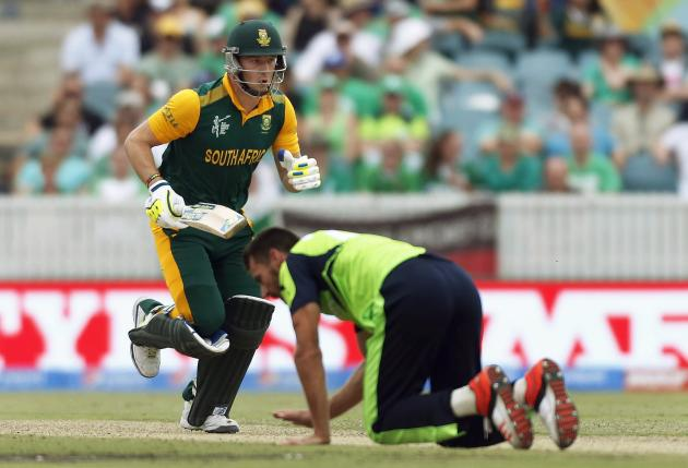 Ireland's Max Sorensen falls over as South Africa's David Miller runs between wickets during their Cricket World Cup match at Manuka Oval in Canberra