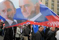 People carry a banner with portraits of Russia's President Vladimir Putin (L) and Prime Minister Dmitry Medvedev during traditional May Day Trade Unions rally in central Moscow on May 1, 2013. When Putin returned one year ago to the Kremlin, Russia could boast robust if unspectacular growth, but in just 12 months, growth has slipped to the extent that Russia risks entering recession