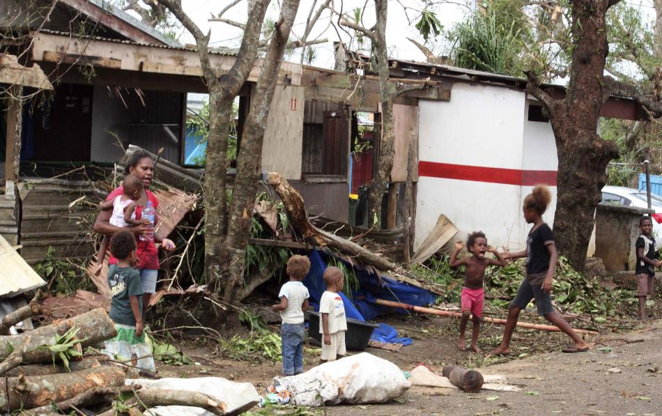 A woman carrying a baby stands with children outside homes damaged by Cyclone Pam, on a street surrounded by debris in Port Vila, the capital city of the Pacific island nation of Vanuatu