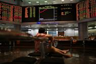 A man watches stock share index movements on a digital display screen in Kuala Lumpur, on May 6, 2013. Malaysia was among the world's IPO leaders last year and the pace looks set to pick up again with tense elections out of the way and expectations that the government will push a reform agenda