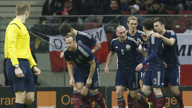 Scotland's players  celebrate after scoring a goal against Poland  during a friendly soccer match between Poland and Scotland in Warsaw, Wednesday March 5, 2014