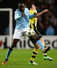 Manchester City's Ivorian defender Yaya Toure (L) vies with Borussia Dortmund's Polish forward Robert Lewandowski during the UEFA Champions League football match between Manchester City and Borussia Dortmund at the Etihad stadium, in Manchester. The match ended in a 1-1 draw