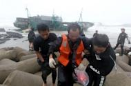 South Korean coast guards rescue a crew member (C) from a Chinese fishing boat stranded off Jeju island on August 28. South Korean rescuers Wednesday recovered two more bodies near two wrecked Chinese fishing boats, bringing the confirmed death toll from a powerful typhoon to 18
