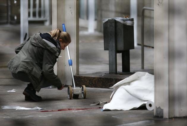 Police officer examines crime scene next to covered body at entrance to courthouse in Frankfurt