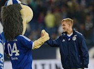 This picture taken on October 6, 2012 shows Lewis Holtby and the Schalke mascot Erwin celebrating after beating Wolfsburg. Holtby will join Spurs in July, despite reported interest from their Premier League rivals, Arsenal, Liverpool and Everton, and he has said he wants to win titles with Tottenham, having been impressed by manager Andre Villas-Boas