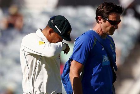 Australia's Usman Khawaja reacts as he walks off the ground with a team trainer after suffering an injury during the second day of the second cricket test match against New Zealand at the WACA gro