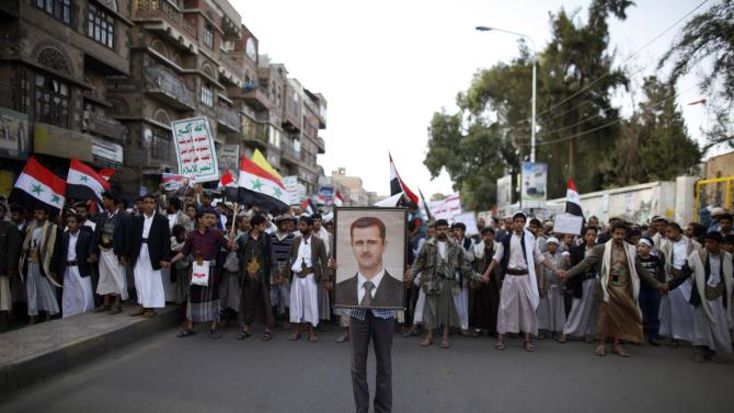 A protester holds a poster of Syria's President Al-Assad during a demonstration against potential strikes on the Syrian government, in Sanaa