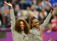 US Serena Williams (L) and Venus Williams celebrate on the podium after receiving their gold medals for winning the London 2012 Olympic Games women's doubles tennis tournament, at the All England Tennis Club in Wimbledon, southwest London
