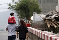 Local residents walk past damaged houses in Longmen on April 21, 2013