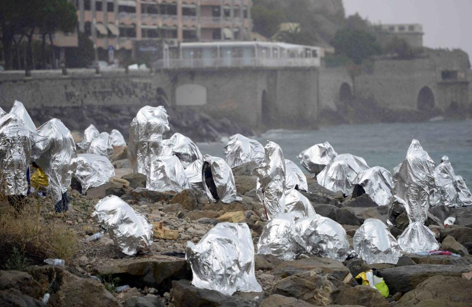 A group of migrants  protect themselves from the weather with emergency blankets on the seawall at the Saint Ludovic border crossing on the Mediterranean Sea between Vintimille, Italy and Menton