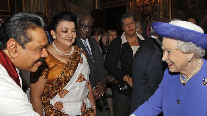 FILE - This is a Wednesday, June 6, 2012 file photo of Britain's Queen Elizabeth II, right,  as she shakes hands with Sri Lanka President Mahinda Rajapaksa, left, as his wife Shiranthi  Rajapaksa, center, looks on, during a reception prior to a lunch with Commonwealth Nations Heads  of Government and representatives of the Commonwealth nations in central London. Queen Elizabeth II will skip the Commonwealth heads of government meeting in Sri Lanka later this year _ the first time she's missed the biennial gathering since 1971, Buckingham Palace said Tuesday May 7, 2013.  (AP Photo/Lefteris Pitarakis, pool, File)
