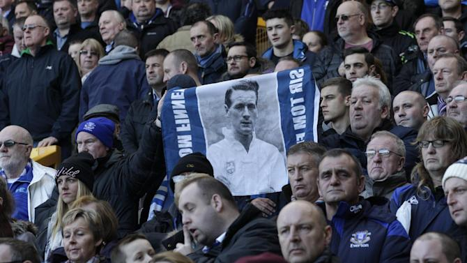 Supporters hold up a picture of Sir Tom Finney who has died at the age of 91 during a tribute to the former England player before Everton's English FA Cup fifth round soccer match against Swansea City at Goodison Park Stadium, Liverpool, England, Sunday Feb. 16, 2014. Finney made more than 400 league appearances for Preston North End between 1946 and 1960