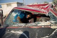 A man removes his belongings from his destroyed car at the site of an airstrike by a Syrian government jet fighter in the northern town of Aazaz, near the northern restive Syrian city of Aleppo