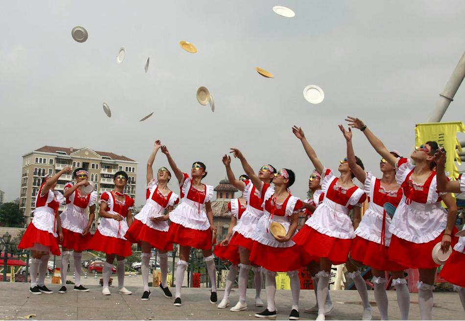 Male staff members of an amusement park wearing maid costumes throw chinaware into the air to be smashed during an event promoting their stress-release activities to mark World Mental Health Day, in H