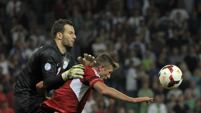 Slovenia's goalkeeper Handanovic is challenged by Cani of Albania during their 2014 World Cup qualifying soccer match in Ljubliana