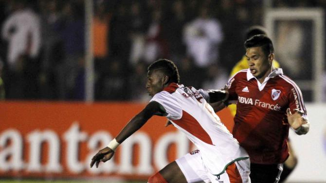Arboleda of Ecuador's LDU de Loja fights for the ball with Gutierrez of Argentina's River Plate during their Copa Sudamericana soccer match at Reina del Cisne stadium in Loja