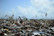 A surivor walks among the debris of houses destroyed by Super Typhoon Haiyan in Tacloban in the eastern Philippine island of Leyte on November 11, 2013