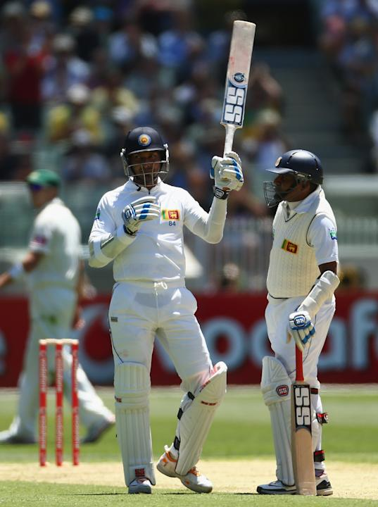Kumar Sangakkara of Sri Lanka raises his bat after reaching tenthousand career runs during day one of the Second Test match between Australia and Sri Lanka at Melbourne Cricket Ground on December 26,