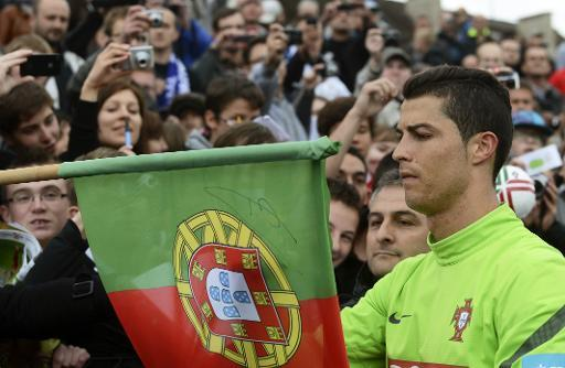 Cristiano Ronaldo signs a Portuguese flag after a training session in Opalenica on June 5, 2012 before Euro 2012