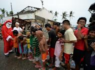 A volunteer dressed as Santa Claus distributes gifts to survivors of Super Typhoon Haiyan in Tacloban, Philippines on December 25, 2013