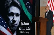 """Mohamed al-Megaryef, president of Libya's ruling national assembly, speaks during a ceremony to honor the late US Ambassador to Libya Christopher Stevens in Tripoli. The sign reads, """"Thanks Chris""""."""