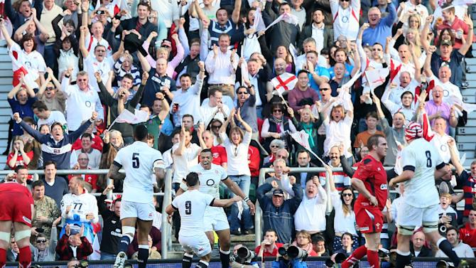 England's Luther Burrell, center, celebrates with his teammates after scoring a try against Wales during the Six Nations Rugby Union match between England and Wales at Twickenham stadium in London Sunday, March, 9, 2014. (AP Photo/Alastair Grant)